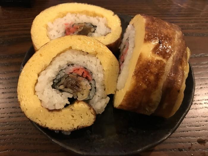 """「太巻き寿司」は、""""ハレの日""""に欠かせない房総の郷土食です。このコーナーには、常時数種の太巻きや寿司弁当が並んでいますが、特に人気なのが、分厚い玉子焼きで巻いた「卵巻き」。酢飯とふんわり甘い玉子焼きのバランスが素晴らしいと評判です。"""