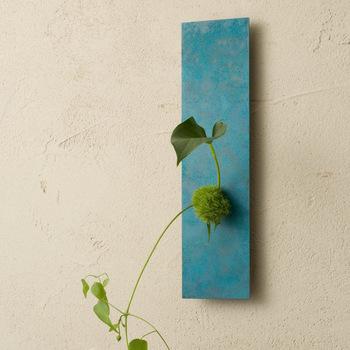シンプルな壁掛けの花器にも、全く違う色合いが揃っています。背面に細いビンを差し込む枠が付いているので、水が必要な植物も気軽に飾れますよ。