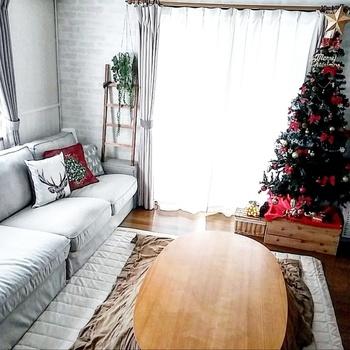 ナチュラルなインテリアには合わせにくいかも…と思いますが、そんなことはありませんよ。  こちらのお家では、クッションカバーにクリスマスモチーフを、そして赤を挿し色に。大きなツリーの土台には、木箱を使って、統一感のある素敵なお部屋に仕上げています。  ツリーは緑色なので、大きくてもナチュラルインテリアになじみやすいですね。