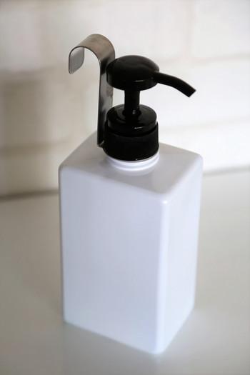 """ちなみにこちらは、食器用洗剤を入れたセリアのポンプボトルです。写真のように、ボトル口のネジ部にフックを固定して使用します。洗剤のボトルを浮かせて収納したことで、キッチンのお掃除がラクになったそうですよ。洗剤の容器やボトルを置かずに""""吊るす収納""""に変えたい方は、ぜひ「ボトルハンギングフック」を取り入れてみてはいかがでしょうか。"""