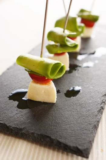 カプレーゼをおしゃれなピンチョスに仕立てて。アボカドをピーラーで剥いて、クルンとリボン状にするのがポイントです。