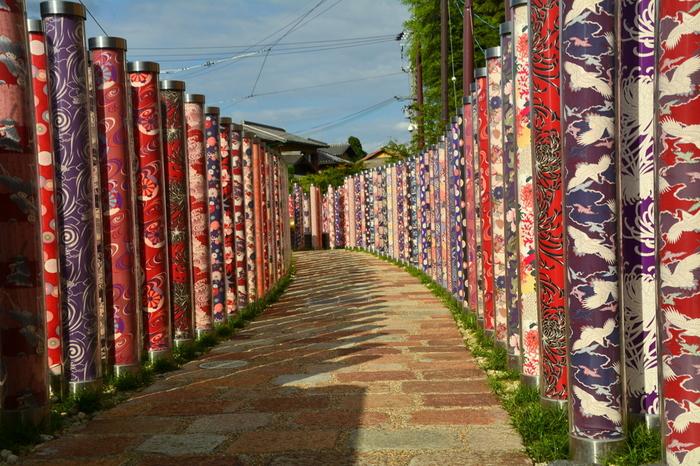 嵐山の最寄り駅は、JR・嵯峨嵐山駅、京福電鉄・嵐山駅、阪急・嵐山駅、の3つあります。それぞれ近接していますが、出発地や目的地によって下記のように使い分けましょう。  ・JR・京都駅から行く場合、またはトロッコにトロッコ嵯峨駅から乗る場合はJR・嵯峨嵐山駅 ・四条・烏丸方面から行く場合、または渡月橋・天龍寺に行く場合は京福電鉄・嵐山駅 ・四条・烏丸方面から行く場合、または嵐山温泉に行く場合は阪急・嵐山駅  画像は、京福電鉄・嵐山駅にある「キモノ・フォレスト」。色鮮やかな京友禅の柱が何本も立てられています。