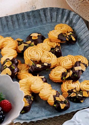 絞り出しクッキーの利点は、絞り袋一つで色々な形にできる事。ハート型やバトン型(短い棒状)も絞りやすいシルエットでおすすめです。さらに、チョコレートをコーティングすれば、シックで上品な雰囲気に仕上がります。