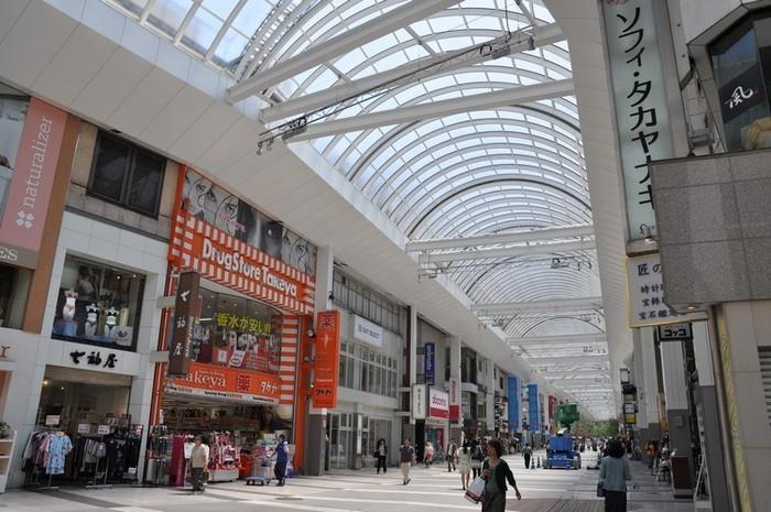 熊本市内で一番賑わう「上通・下通」。市電通町筋電停から歩いて1分の場所にあります。上通・下通は道路を挟んだアーケード街で、南九州随一の商店街としても知られています。新旧のお店がずらりと連なり、いつ訪れても賑やかで楽しい場所。