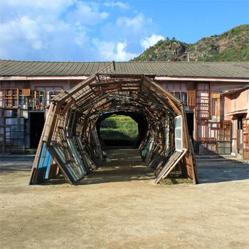 豊島には島の自然に溶け込んだようなアート作品が数多くあります。こちらは塩田千春さんの「遠い記憶」。  旧集会場に、使われなくなった約600枚の建具で制作されたトンネル状の立体作品。トンネルは建物を貫くように伸びていて、正面に水田が、振り返ると海が見える造りに。