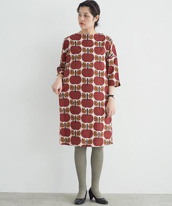 レトロな生地で手作りしたかのようなリンゴ柄のプリントワンピース。厚手のタイツとパンプスで、まるで70年代のような着こなしが素敵です。