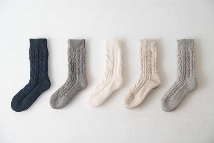 """秋冬はお洒落が楽しい季節。しっかりと寒さ対策をしながら、さりげなく足元のお洒落を楽しみましょう! わざわざオリジナルの""""アランウール靴下""""は、長野県の靴下メーカー""""株式会社タイコー""""とコラボし、ホールガーメントという製法で編まれています。丈夫で長持ちするのは勿論、履き心地の良さを追求し、試作を何度も繰り返し、製造されています。 こちらの靴下の魅力は、なんといっても履いた時の暖かさ。まるで湯たんぽを履いているように足元がポカポカに!高級ウール糸を贅沢に使用し、アランをモチーフに、まるで手編みのような贅沢な風合いです。 パンツの裾からチラッと見えた時に、さりげない可愛さを演出してくれる靴下。カラーは、左からネイビー、モカ、スノーホワイト、オートミール、霜降りグレーの5色。"""