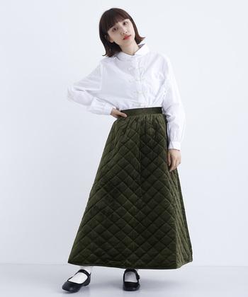 ベロア素材のフレアスカートに、キルティングステッチを施した一枚。白シャツをタックインして、個性派アイテムを上品に着こなしています。