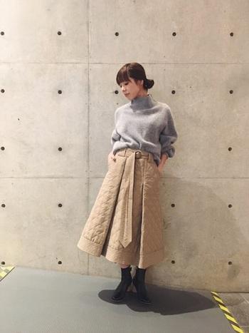 たっぷりとフレアを施したボリューミーなキルティングスカートは、秋冬コーデの程よいアクセントにもぴったり。グレーのニットをゆるくタックインして、バランス感を意識したコーディネートの完成です。