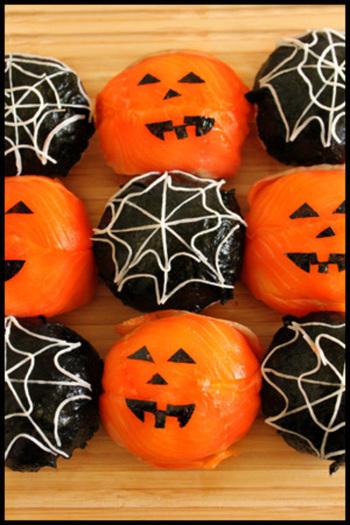 ぱっと目を引くまあるいおにぎりで食欲もアップ!?ジャックランタンのかぼちゃ顔は、スモークサーモンでできていて、切り抜いた海苔でパーツを象ったもの。もう一つのクモの巣にはカニカマが使われています。