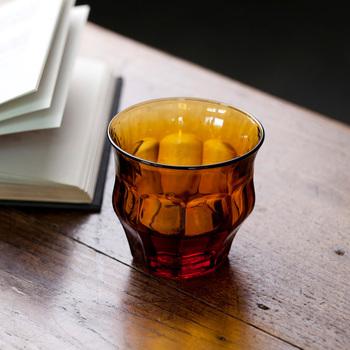 """高温の窯で再溶解させて変形させた「ティプシーグラス(TIPSY GLASS)」。""""TIPSY""""とは""""ほろ酔い""""という意味。変形具合は1点ずつすべて異なり、同じものがひとつもないのも魅力。シックなアンバーカラーも、ゆっくりと愉しみたい秋のお酒にぴったりです。"""