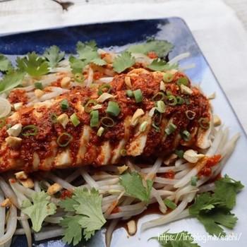 レンジ加熱したもやしの上にサラダチキンを置いて、食べるラー油で作ったソースをかけただけのよだれ鶏。パクチーやナッツなどをトッピングすると本格的に見えます。