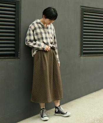 さりげなくフレアシルエットになっている、カーキカラーのキルティングスカート。上品にも着こなせますが、ネルシャツやスニーカーでとことんカジュアルにまとめるのもおしゃれですね。