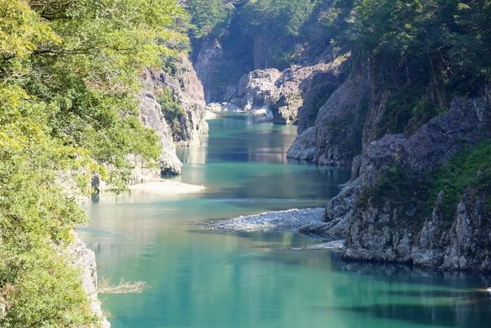 エメラルドグリーンの水面と荒々しい岩肌が織り成す見事な景色が堪能できる瀞峡。川舟に乗ってゆったりと巡ることができます。