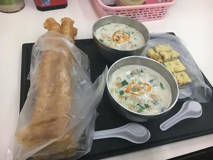 真ん中が「鹹豆漿」(豆乳スープ)、右が台湾の卵焼き「蛋餅」、左が揚げパンです。  揚げパンは豆乳スープに浸して食べるとさらに美味しくいただけます♪ (ローカルの方で、2本の揚げパンを同時にディップする強者さんもいらっしゃいます)  他にも肉まんやおにぎりなどがあります。  筆者もこちらのメニューをいただきましたが、見た目よりも朝の体にひびきにくく、とても美味しくいただけました!