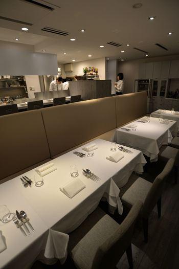 """高低差を利用した店内は、キッチンのすべてが見渡せる""""シェフズテーブル""""なカウンター席とテーブル席の二段構え。"""