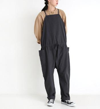 ゆるっと着られる黒のサロペットに、ベージュのブラウスを合わせたコーディネートです。カジュアルな印象を与えるサロペットなら、ブラウスやシャツを合わせるだけできちんと感をプラスできます♪