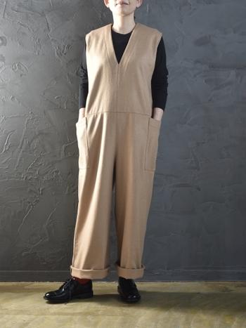 「大人のつなぎ」というテーマで作られたベージュのサロペットは、一枚で着るだけでスタイリッシュ見せが叶うアイテム。黒インナーとマニッシュなシューズを合わせて、大人のリラックスタイルに。