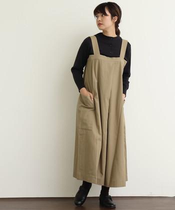 綿素材で長いシーズン活用できるベージュのサロペットは、ワイドパンツスタイルでゆったりと着られる一枚。サロペット以外は全て黒でまとめれば、引き締め効果で着太りも回避できます。