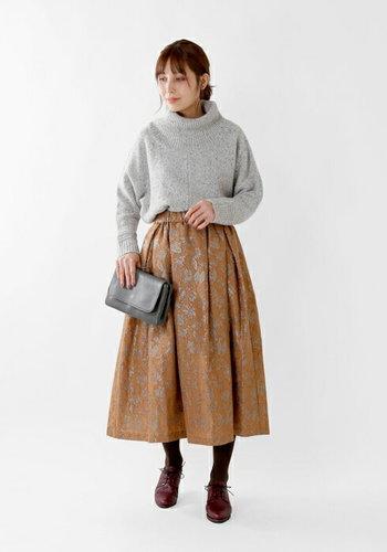 タートルネックのニットを、メタリックのジャガードデザインがレトロな印象のフレアスカートにタックイン。小ぶりなクラッチバッグで、パーティー感を演出しています。