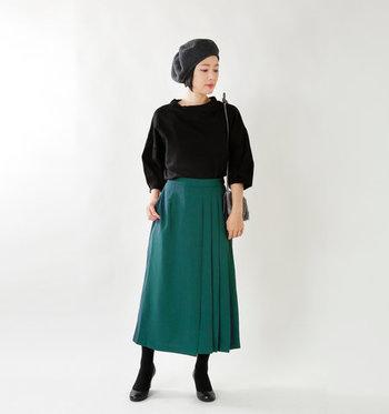サイドにプリーツが入ったロングスカートは、深みのあるグリーンがキレイめな印象に。黒トップスとベレー帽が、きちんと感を演出し過ぎずおしゃれな雰囲気にまとめています。