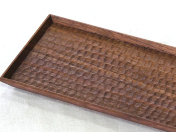 こちらは『長方平皿(ウォールナット はちのす)』という作品。蜂の巣のような六角形の模様が美しく並んだ平皿です。 料理を載せる以外にも、お茶のセットを並べたりアクセサリーをディスプレイしたりと、自分に合った使い方ができます。