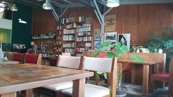 ランチには3種類から選べる中国茶がつきますが、自家焙煎珈琲もおいしいお店です。  木の床やテーブル、置かれたグリーンもあいまって、リラックスしてくつろげる心地いい空間になっています。  本棚には本がぎっしり。オーダーしたメニューが届くまで読書をして過ごすのも◎。