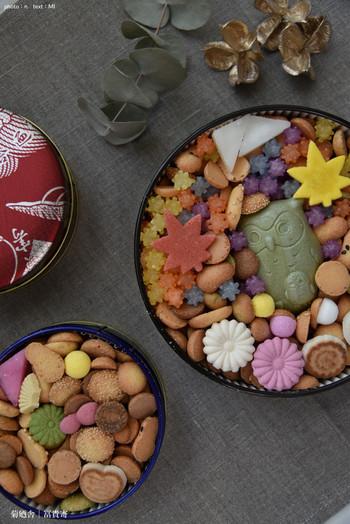 銀座菊廼舎は明治23年創業の100年を超える江戸和菓子の老舗です。代名詞とも言える「冨貴寄」は贈り物に最適ですよ。 缶を開けたら小さな可愛らしい江戸菓子がびっしり詰まっていて、思わず笑顔なる逸品です。  写真は(左から)通年商品の赤、青2つの小丸缶と季節限定のふくろう缶がセットになった秋の季節缶ギフト。