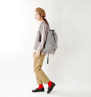 シンプルなベージュ系ワントーンコーデに赤いソックスを合わせて遊び心をプラス。黒×赤でコントラストを強めて印象的な足元に。