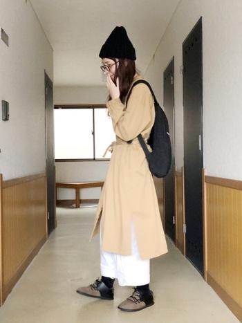 ベージュのシャツワンピースとホワイトのワイドパンツを合わせた、柔らかなレイヤードスタイル。黒のニット帽をプラスすれば着こなしにまとまりが生まれます。