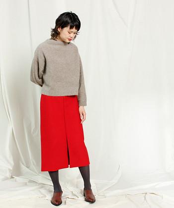 パッと目を引くレッドのタイトスカート。ブラックよりもソフトなグレータイツなら、色のコントラストがつき過ぎずまとまりのいい着こなしに。
