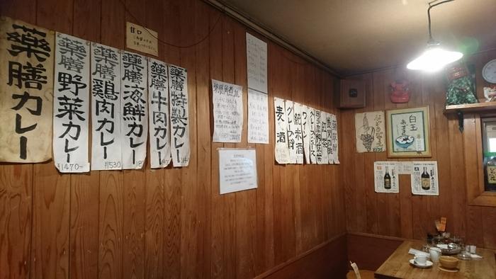 こぢんまりとした店内はどことなくレトロな雰囲気が漂います。壁には味わい深い文字で書かれているメニューが掲示されています。薬膳カレーだけでなく、ワインや純米酒などのアルコールメニューも。