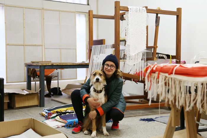 若手の作家には、昔ながらの手仕事をリスペクトして活かしながらユニークでサステナブルなモノづくりをしている人が多く、魅力を感じています。それがポルトガルの作家さんの特長のひとつかもしれません。  写真/セリア・エステヴェシュと愛犬のシュシュ。伝統的な織の技術を用い、世界各地のアーティストやイラストレーターとコラボレートしてグラフィカルでユニークなラグを製作しています。仕事場でもどこでも、大きなシュシュと一緒。