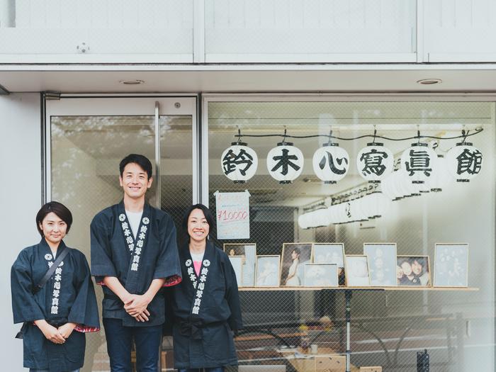 撮影のサポートと、今回の取材風景を撮影してくれた齋藤さおりさん(左)。鈴木さんを囲み、写真館の前で