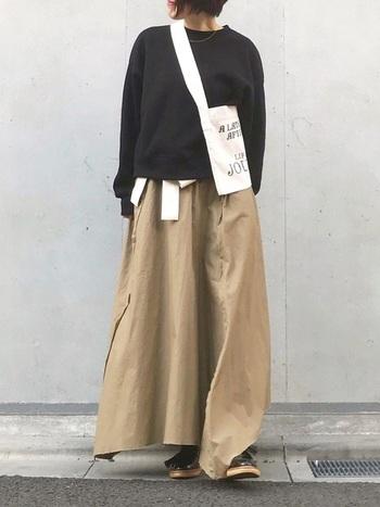 黒いトップスに、ボリュームたっぷりのロングスカート。シンプルなスタイルに、エナメルシューズが足元にもボリュームと存在感をプラスしてくれます。