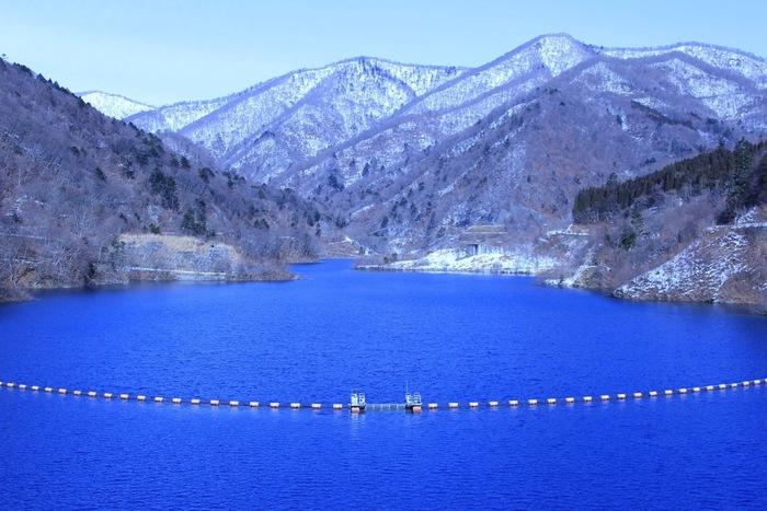 """群馬県を代表する温泉、四万(しま)温泉の奥にある人造の湖が「四万湖(しまこ)」と「奥四万湖(おくしまこ)」です。どちらの湖も、""""四万ブルー""""と呼ばれる水の色が美しいスポット。なぜ、水が青く見えるのかは諸説ありますが、一説には湖に含まれるアロフェンという物質が反射しているといわれています。"""