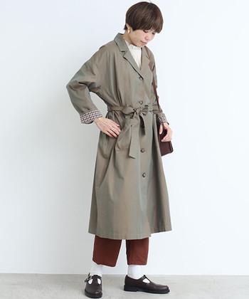 ちょっぴりオーバーサイズのトレンチコートは、ウエストのリボンベルトを巻いてガウン風に着こなしても◎袖を折り返すと裏地のチェック柄が覗き、秋冬らしいブラウンパンツとの相性も抜群です。
