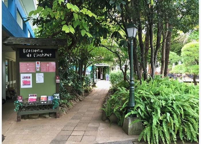 JR飯田橋駅で降りて外堀通りを横断し、坂を上って5分ほど。フランス政府の管理・運営による日仏交流施設・アンスティチュ・フランセ東京(旧東京日仏学院)内にあるブラッスリー(アルコールメニューのある食堂)。お店まで、緑濃いアプローチが続いています。