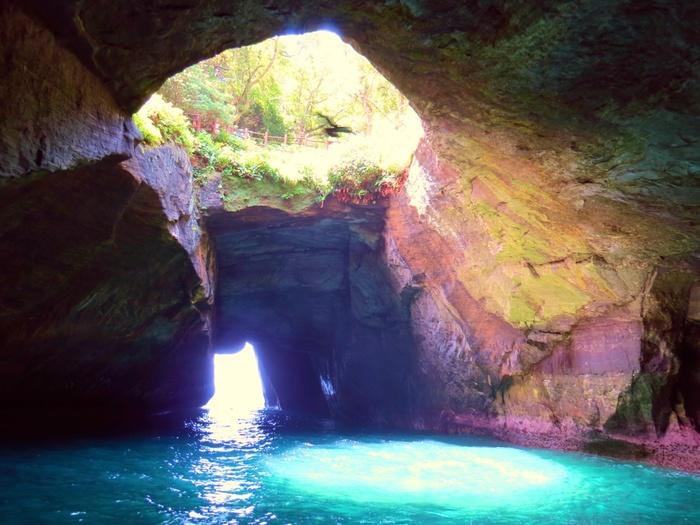 洞窟の天井は風化によって丸く抜け落ちていて、下から見上げると空の青さと周りの緑が見えます。季節や時間、天候によって水の色がさまざまに変化するそうで、何度訪れてもその美しさに息をのむほど。
