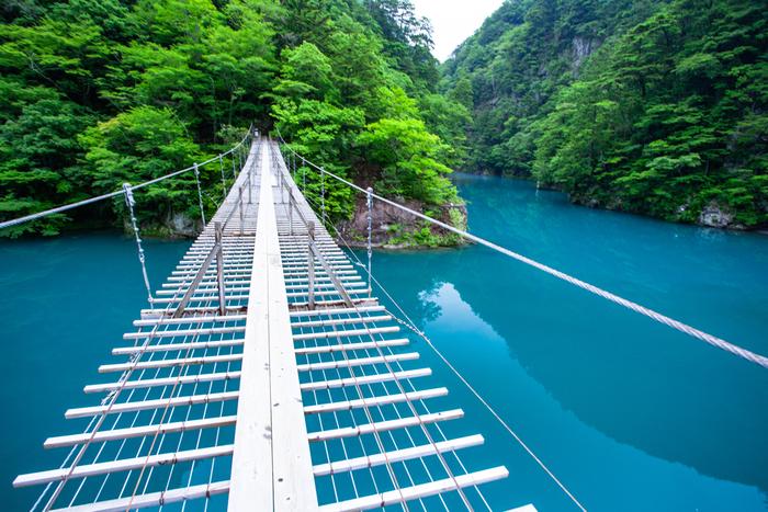 """ここがスタート地点。かなり細い橋なのでスリル満点ですが、両側に目を移すとコバルトブルーの美しい水面が!水が青く見えるのは、澄んだ水にわずかな微粒子が溶け込んで反射する""""チンダル現象""""によるもの。吸い込まれそうな青い湖面を眺めながら、ゆっくりと足を進めましょう。"""