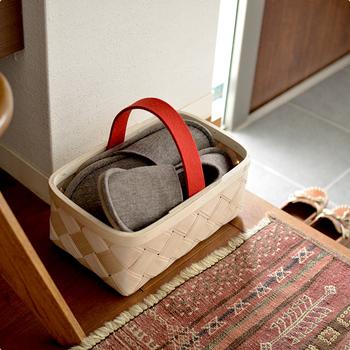 お客様のスリッパをカゴに入れて。かさばらずに片付けられ、持ち手があるから掃除の時の移動もラクラクです。