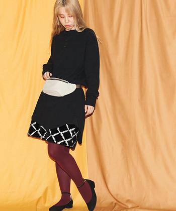 ニット×スカートのシンプルな着こなしを、カラータイツが個性的に昇華。色はシックな艶やかさを演出するパープルを選んで。