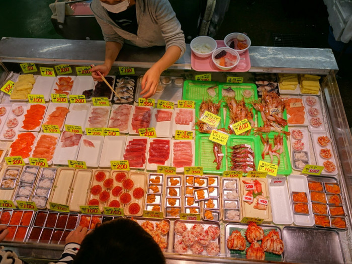 北海道の「釧路和商市場」では、「勝手丼」と名付けられた自分で好きな具を選べる海鮮丼が名物です。その流れはいたってシンプル。市場の惣菜屋さんでご飯を購入し、好みのネタを選んで、最後に醤油をかけてもらって出来上がり!カニ汁や漬物なども一緒に購入できます。