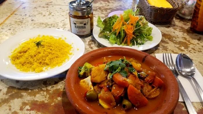 国際色ゆたかなメニュー、たっぷりつけてくれる野菜が特色。お茶では、コーヒーやティーのほか、モロッコのミントティや蓮のお茶などが揃っています。上映中の作品にちなんだお料理が登場することもあります。 ※画像は『野菜とオリーブのクスクス』。お好みで唐辛子が効いた北アフリカの調味料・アリッサを振っていただきます。