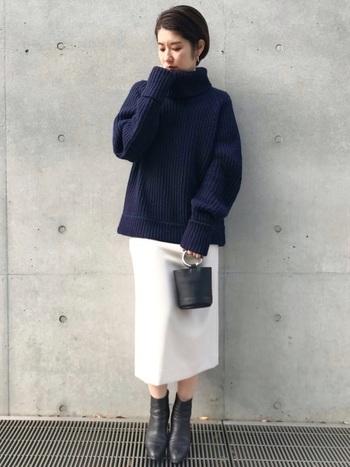 上品な白いスカートが目を引く、おしゃれな冬の大人スタイル。シャープで女性らしい印象のタイトスカートは、ゆったりしたオーバーサイズニットとの相性も抜群です。ブーツやバッグなど、シックな小物使いも素敵ですね。