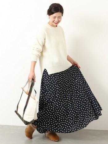 ざっくりとした風合いの軸編みニットと、女性らしいドット柄のスカートを組み合わせたおしゃれなコーディネートです。白×黒のシックなモノトーンの配色も、大人っぽい雰囲気で素敵ですね。