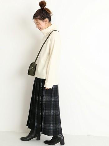 シンプルなタートルネックのプルオーバーに、クラシカルなチェック柄スカートを合わせた上品な着こなしがおしゃれですね。シックで女性らしい雰囲気のコーディネートは、冬のお出かけや旅行シーンにもぜひおすすめです。