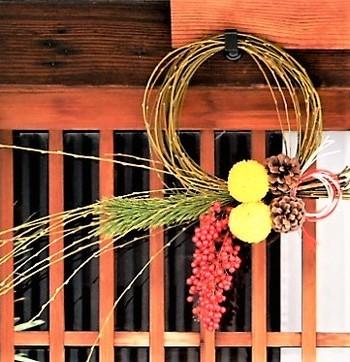 枝でシンプルな輪を作り、松や木の実を飾り付けたしめ飾り。さりげなく素朴な雰囲気が素敵です。