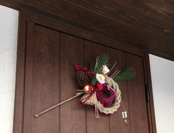 カラフルな紐や松を飾り付けた小ぶりなしめ飾り。趣のある木のドアに飾れば、お正月を気持ちよく迎えられそうですね。