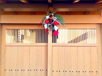格子戸が素敵な木の戸に、赤白が鮮やかな大きなしめ飾りが存在感を放っています。凛とした雰囲気で、玄関先がぱっと華やぎます。